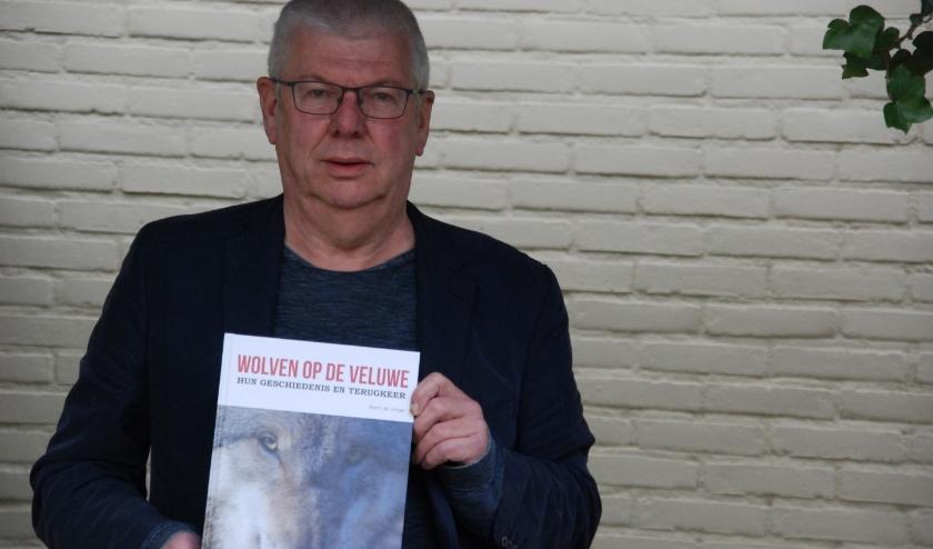 Auteur Foto Evert de Jonge met zijn boek 'Wolven op de Veluwe – Hun geschiedenis en terugkeer'. (foto: Ton Brands)