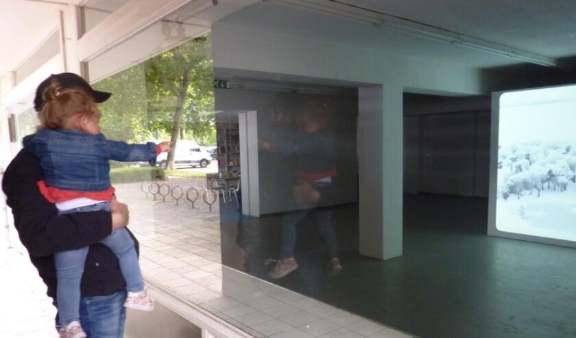 Buurtbewoners kijken naar de videoinstallatie van Jeroen Eisinga achter de ramen van Motel Spatie bij winkelcentrum Presikhaaf.