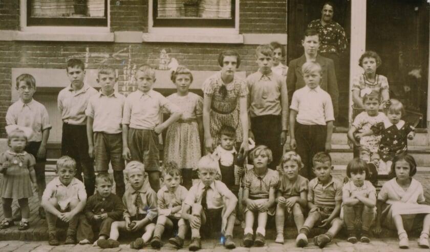 <p>Albert de Koning, zittend derde van rechts, groeide op in de kinderrijke omgeving van de Pieter Karel Drosaarstraat. Foto: Priv&eacute; archief </p>