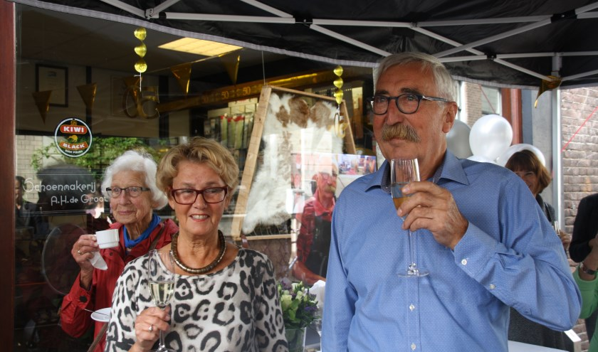 Het echtpaar De Groot proost op het vijftigjarig bestaan van de schoenhersteller in de Nieuwstraat. Bert de Groot was overdonderd door het verrassingsfeest. Foto: Kees Stap
