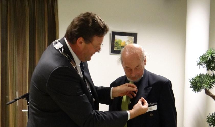 Alphons Devilee krijgt het gemeentelijk waarderingsteken opgesteld door burgemeester Van de Weerd. (Foto: Albert Goeree)