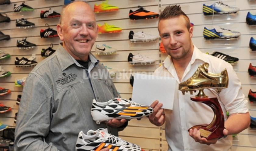 Willy Benerink overhandigt een cadeaubon en de Gouden Schoen aan Kelvin Meijer. De 23-jarige aanvaller van VV Gendringen mag zich voor de tweede keer topscorer van Oude IJsselstreek noemen. foto: Roel Kleinpenning