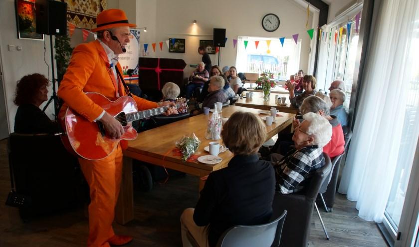 De Oranje Man zorgde voor vertier tijdens het eerste lustrum van de kleinschalige woonvoorziening Klein Houtdijk. Zo zong hij ook even een 95-jarige bewoonster toe.