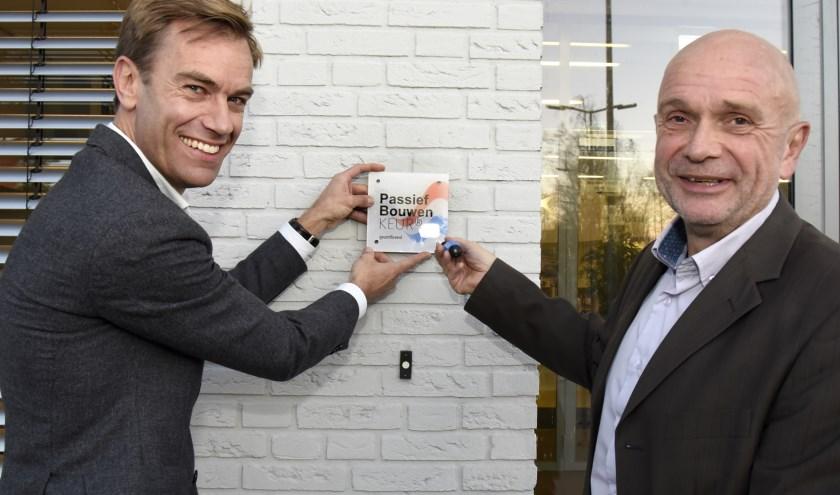 Frank Grootenboer van stichting PassiefBouwen plaatst samen met rector van Tongerloo het muurschildje behorende bij het certificaat. Foto: MP