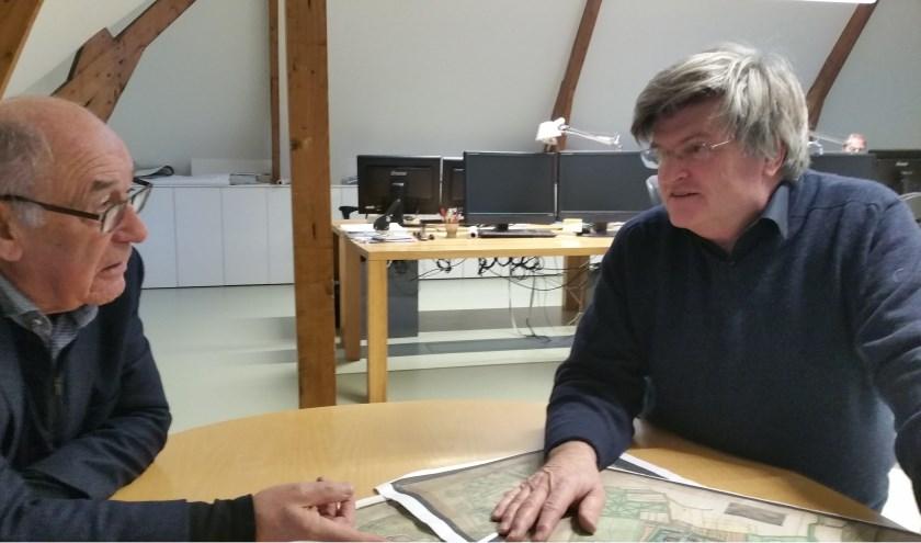 Auteurs Kees Bos (l) en Jan Willem Bosch (r) kijken naar een van de kaarten uit hun Landschapsatlas van de Oosterschelde. Foto: Theo Rietveld