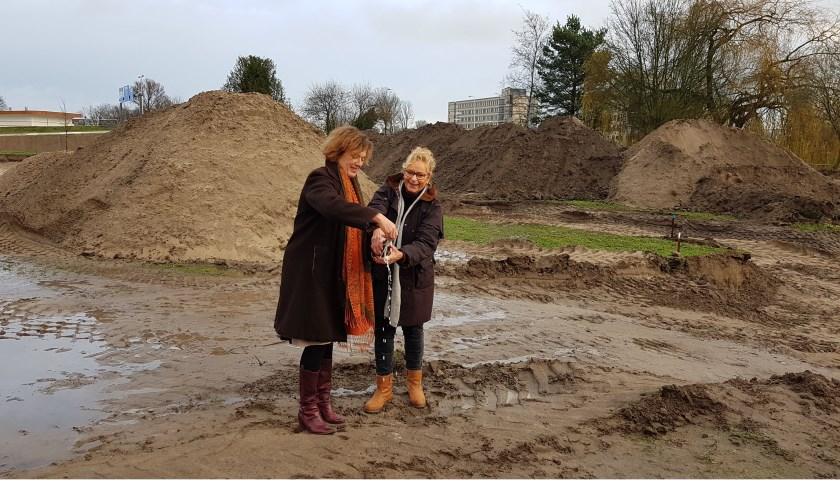 Marijke Oude Tijdhof, toekomstig bewoonster en Liesbeth van Asten, directeur Rentree 'dopen' de grond in het Venenpark waar 13 woningen gebouwd worden.