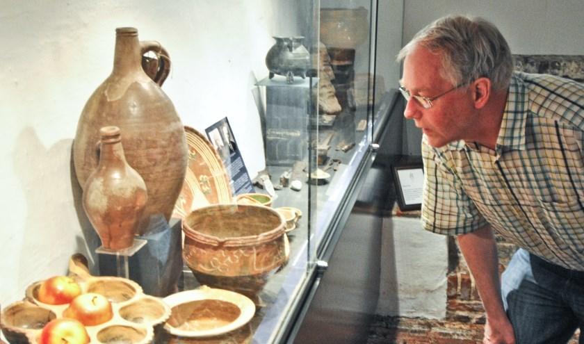 Ron Maat bekijkt de bijzondere collectie aan archeologische vondsten in het Voerman Museum Hattem. Foto Voerman Museum Hattem.