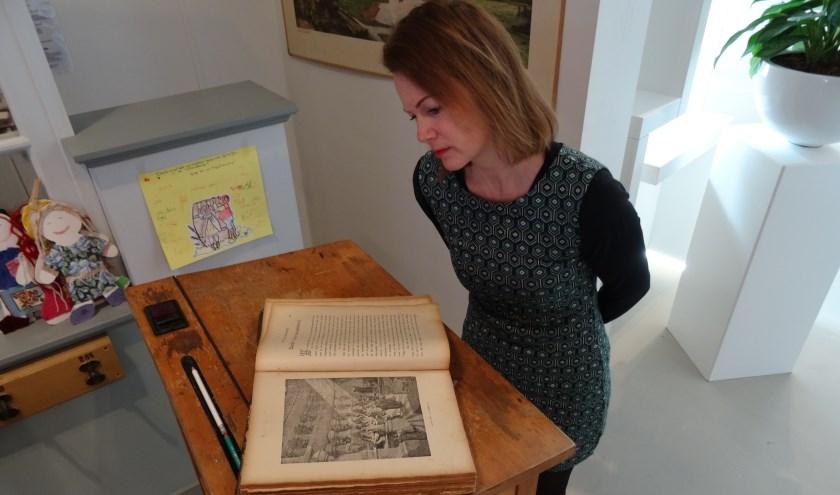 Museumconservator Natalie Kriek bekijkt de bijzondere kinderbijbel die op de huidige jubileumexpositie is te bewonderen. (Foto: MV)