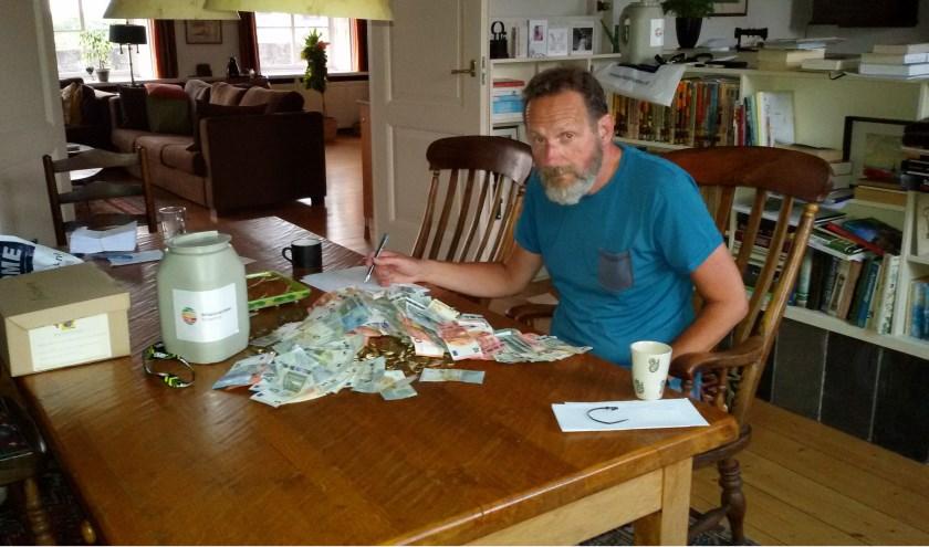 Jan Poulisse telt het geld van de jaarlijkse actie, een record bedrag van 45.000 euro. Foto: Nanda Poulisse