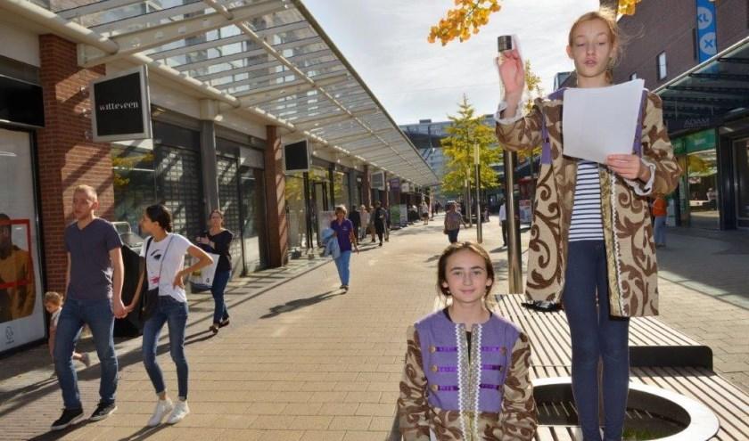 In het zonnige winkelcentrum van In de Bogaard draagt Lieke vd Boom (14) samen met haar vriendin gedichten op aan de wandelende voorbijgangers.