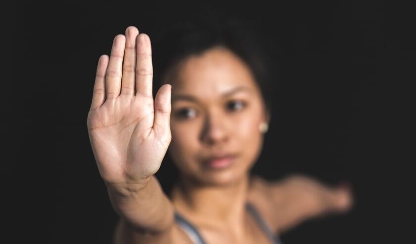 <p>Een vrouw die haar hand opheft als teken: stop het geweld.</p>
