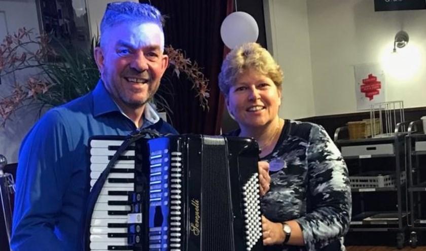John krijgt een accordeon uit handen van welzijnsmedewerkster Desireé.