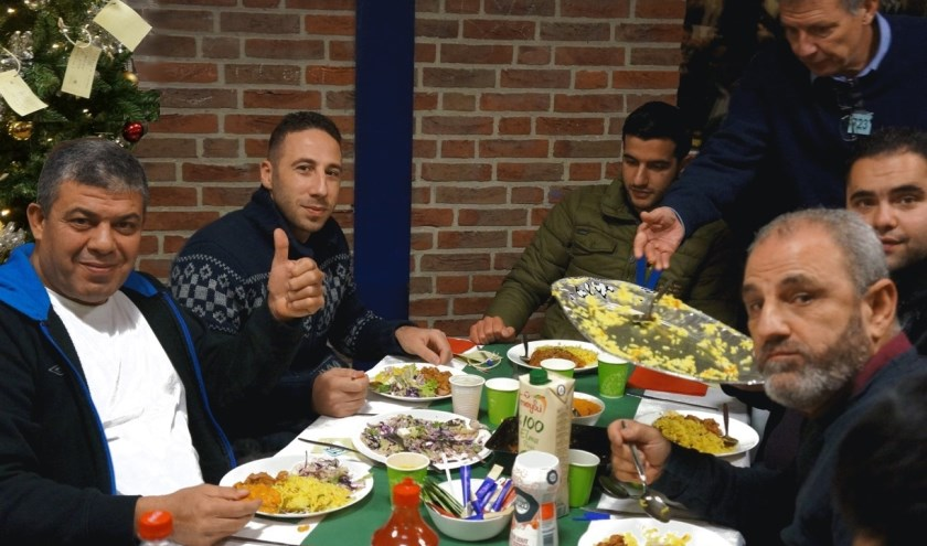 Syriërs aan een van de vijfentwintig gedekte tafels in de eetzaal van de Leemkuil. Achter hen de kerstboom met wensen. (Foto: Pauline Schakenbos)