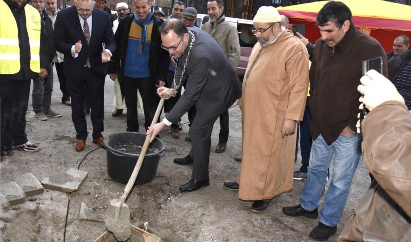 Onder toeziend oog van de voorzitter van MIV Assalam (r) 'stort' burgemeester Milo Schoenmaker het eerste beton voor de nieuwe gevel van het islamitisch centrum aan de Antwerpseweg. Foto: Marianka Peters