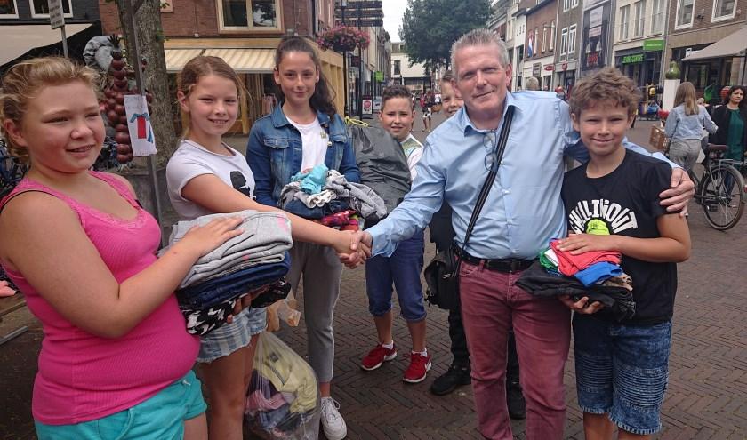 Mario van Keulen van stichting Klesteo ontvangt uit de handen van de Tielse kinderraad stapels met kleding.