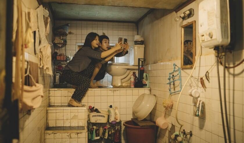 Aan het begin van de film: de arme familie gaat op zoek naar het beste internetbereik in huis. Het washok/toilet blijkt de beste plek...