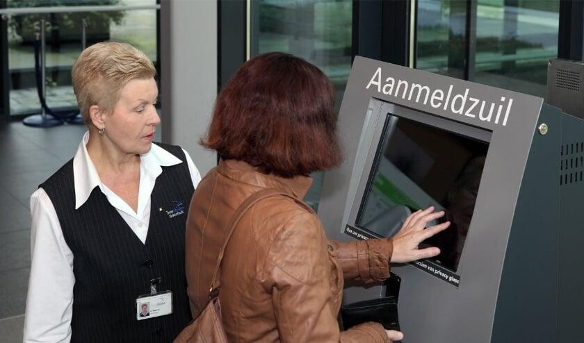 <p>Een gastvrouw biedt assistentie bij een aanmeldzuil, een archiefbeeld van elders in het land.</p>