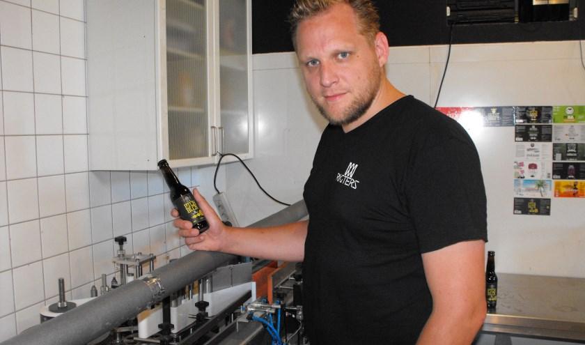 Maarten Nijhof laat een fles zien, die even daarvoor is voorzien van een etiket.