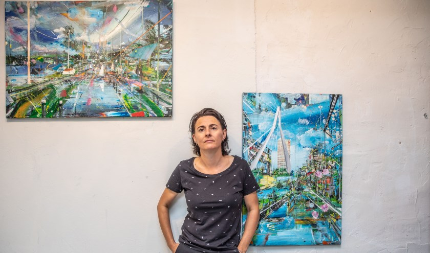 Anneke Wilbrink voor twee van haar kleurrijke doeken in haar atelier aan de Brink.