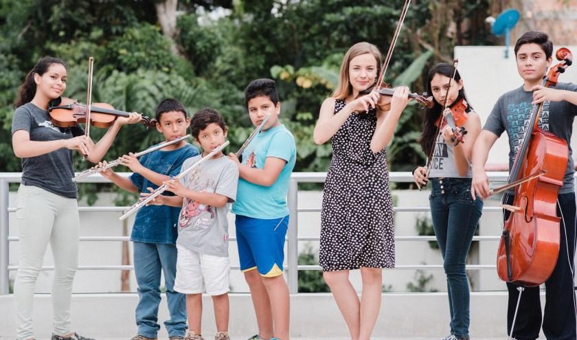 Laura van Essen tussen enkele kinderen van het orkest dat ze startte in haar woonplaats Moyobamba in Peru. (foto: Miguel Sifuentes)