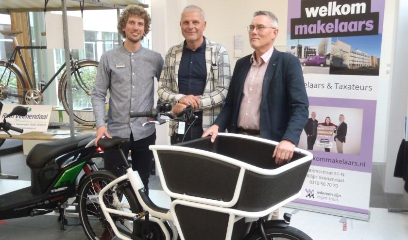 Een medewerker van Tweewielerspecialist Rein Veenendaal (l) toont een geavanceerde electrische fietskar. Voor Dick van den Bos van Welkom Makelaars (m) is het misschien wel iets om in zijn bedrijf te introduceren. (Foto's: Pieter Vane)
