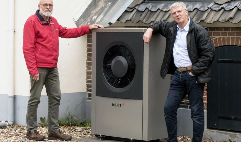 Henk Kasper (rechts) en Ton Holtslag bij een warmtepomp, een alternatief voor gasloos wonen. (foto Auke Pluim)