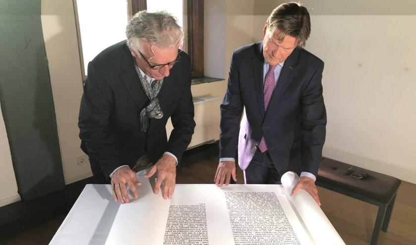 Peter Schoon bekijkt samen met wethouder Piet Sleeking een van de papierrollen. (Foto: Jarko Witte- van Leeuwen)