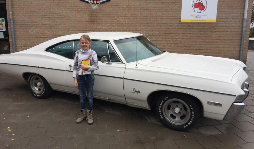 Cato van Turnhout poseert voor een prachtige Chevrolet met haar net gekochte kinderboeken