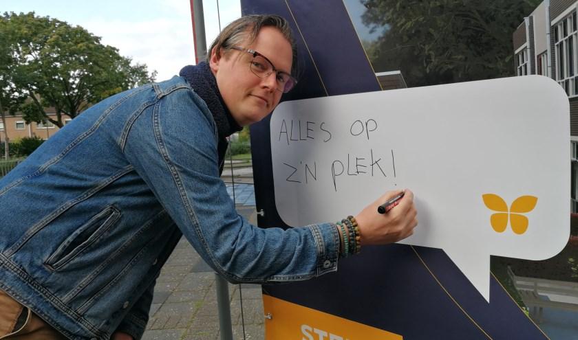 BartJan Burgers zet zijn leus op het canvas doek van de kluswoningen in het voormalige gebouw van de Globeschool (Foto Peter Spek).