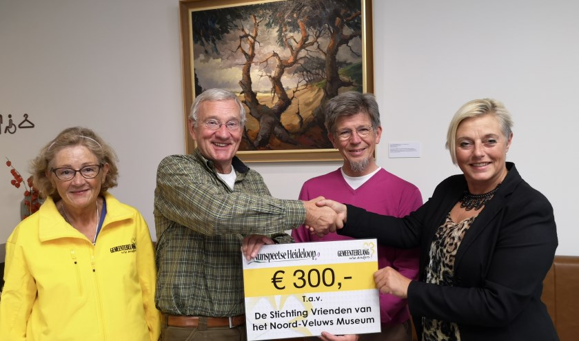 Corrie Jansen (r.), coördinatrice van de Nunspeetse Heideloop reikt de cheque uit. (Foto: Gemeentebelang)
