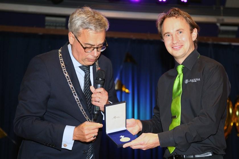 Janus Hermans krijgt de Koninklijke Erepenning uit handen van burgemeester Jan Brenninkmeijer.
