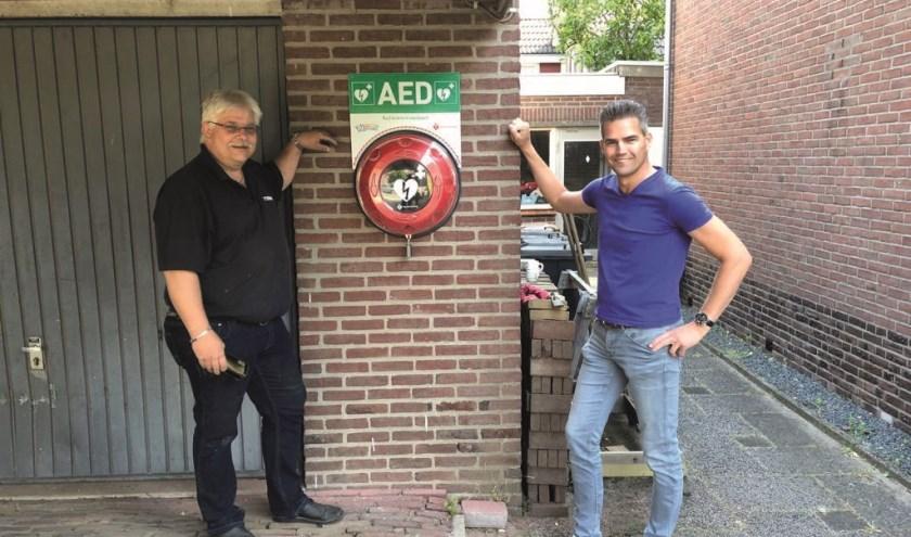 Werner Willems (rechts) bij Geron Hugen in de Julianastraat, die het afdak bij zijn woning beschikbaar heeft gesteld voor het AED-toestel.