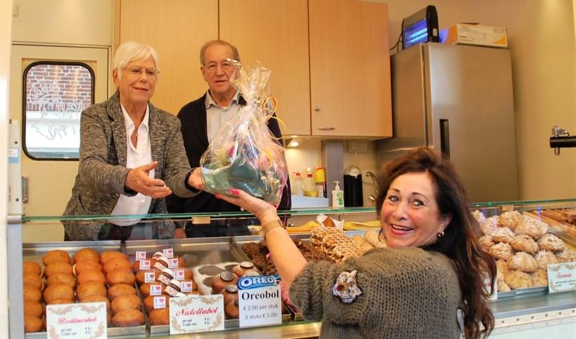 Kermiscollega Mien Eckelboom meldt zich aan de oliebollen- en gebakkraam bij Henk en Ina met een cadeautje namens de exploitanten.