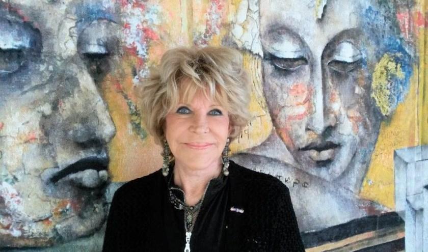 Astrid Engels poseert voor een van haar schilderijen in haar Gooise atelier.