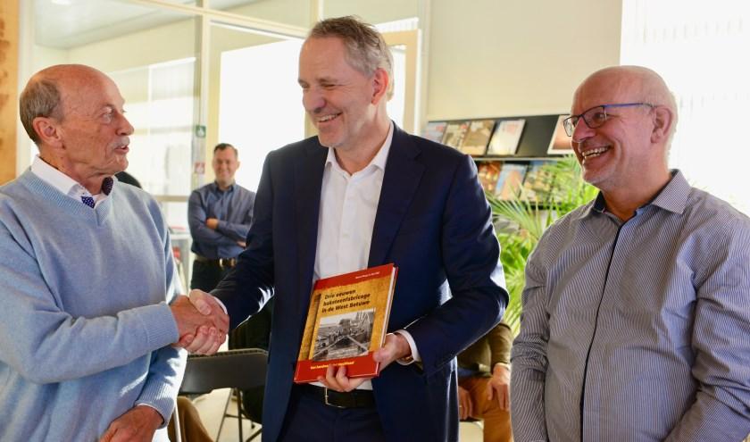 De auteurs overhandigen het eerste boek aan de directeur van de steenfabriek in Haaften (vlnr) Aart Bijl, dhr. Koekoek en Marcel Dings.