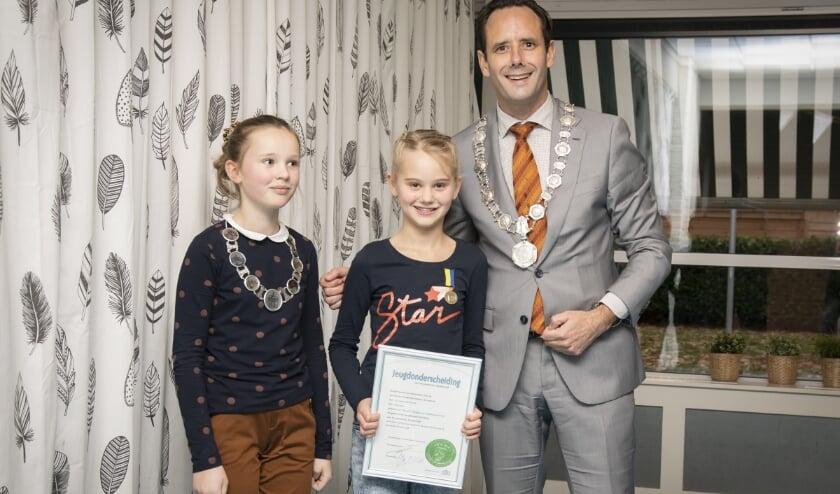 <p>Charlene Galesloot (midden) kreeg op 26 november 2019 het jeugdlintje uitgereikt van de burgemeester en kinderburgemeester. (foto: Ton Pors)</p>