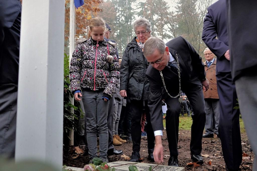 Loco Marco Verloop legt krans. Naast hem de zus van Marietje van Ravenswaaij met haar kleindochter.  © DPG Media
