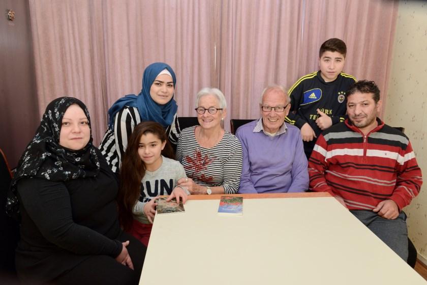 Nel en Klaas Hoornveld temidden van het gezin Mailki, wat ze begeleiden bij het integreren in Nederland.