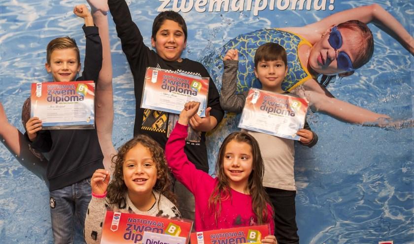 Op de foto tonen Selena, Valentine, Jurre, Djilani en Ekrem trots hun B-diploma na afloop van het afzwemfeest van Sportbedrijf Arnhem in De Grote Koppel.