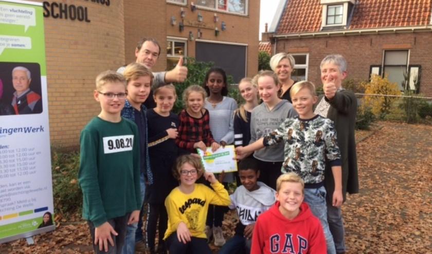 """De overhandiging van de cheque door de directeur Ingrid en enkele kinderen aan leden van de Commissie """"Help Sint Helpen""""."""