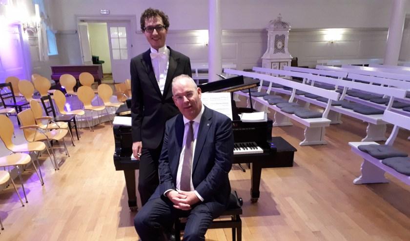 Pianist Wouter Harbers en organist Willem Harold Boog (zittend) Harbers werkt op de vleugel mee aan het jubileumconcert.