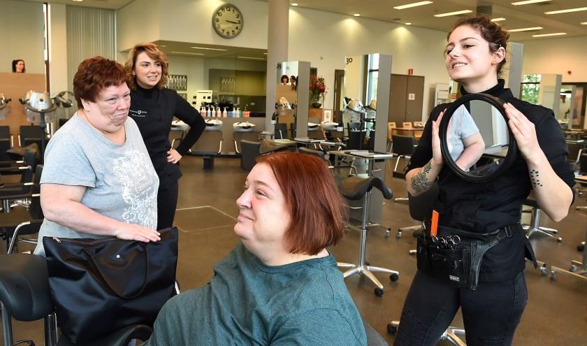 Annet Vriezen, leerling Femke van Eemden en in de stoel Dorothé Hueskes en Alicia Soyer uit Aalten leerling 2de jaars kapersopleiding tijdens de verwendag op Graafschap College. (foto: Roel Kleinpenning)