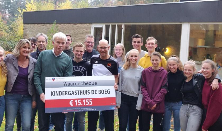 Leerlingen van het Montessori College bij de overhandiging van de cheque aan voorzitter Sjaak Thijssen van De Boeg. Rechts Wilbert Lamers, docent lichamelijke opvoeding aan het Montessori College.