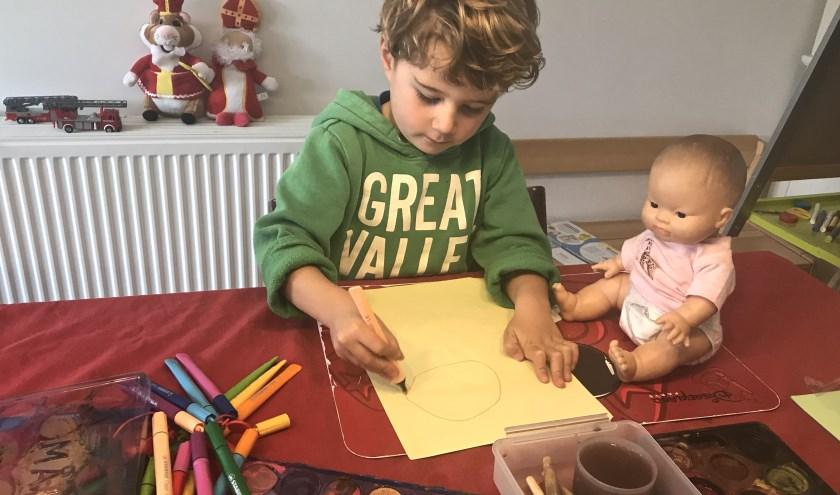 Gijs van Beurden, (3 jaar) is al druk bezig het maken van een mooie tekening. Potloden, verf alles ligt klaar om een mooie tekening te kunnen maken.