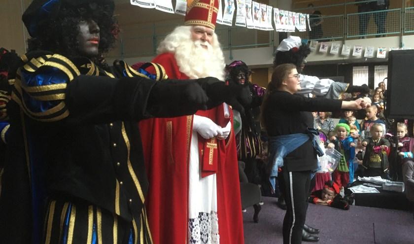 Sinterklaas kijkt tevreden als de pieten met alle kinderen een dansje voor hem doen.