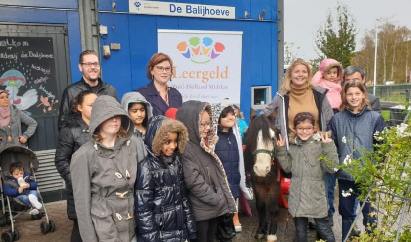 Wethouder Groeneveld samen met enkele kinderen van het project.