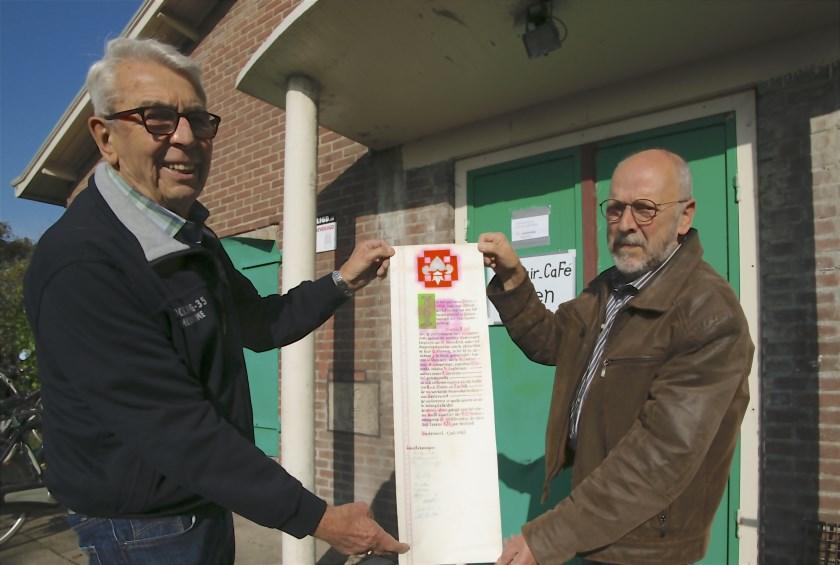 Fotograaf Piet Wijnands van de Westervoort Post (links) en Paul de Klein, wiens vader Jan destijds oubaas van Scouting Westervoort was, tonen de oorkonde, die goed geconserveerd uit de koker tevoorschijn kwam.