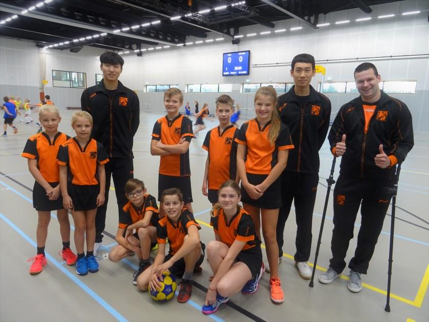 De Chinese korfbal-internationals Suen (links) en Austin komen DKOD, tot eind januari 2020, versterken. Trainer Jaap Jochems en de DKOD-jeugd zijn blij met de komst van het sterke duo.