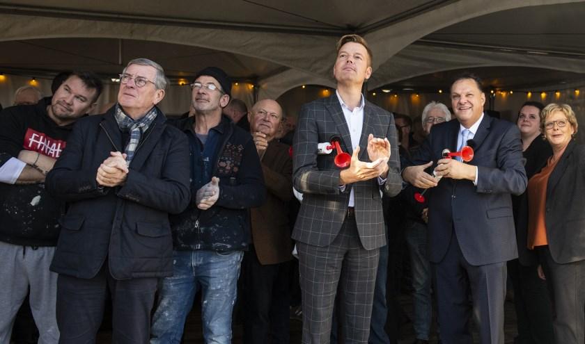 Wethouder Fons d'Haene en directeur Roel van Heugten gaven met toetertjes het sein voor het hijsen van de vlaggen. Foto: Willem Binnendijk