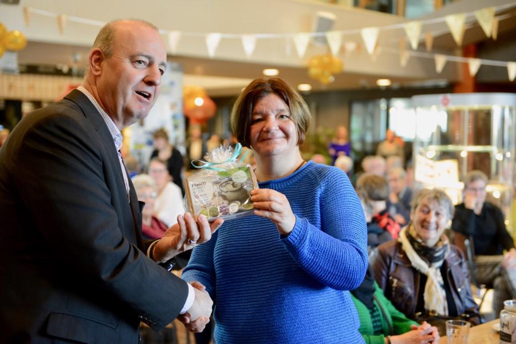 Bianca van Acquoy ontving van wethouder Ton van Maanen als eerste het mantelzorgcompliment een VVV cadeaubon van € 100,-  © DPG Media
